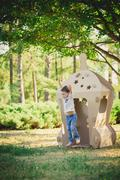 child playing in a cardboard spaceship. Eco concept - stock photo