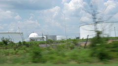 Driving view of large petrochemical storage tanks Stock Footage