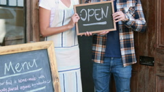 Smiling waitress and hipster man holding open signboard - stock footage