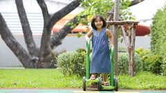 Little asian girl riding fast a push Carting / cart at the playground / park - stock footage