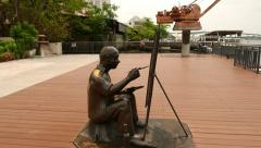 Bronze sculpture of aged painter, sitting on riverbank against canvas Stock Footage