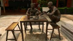 Bronze composition of dockers eating, camera move around Stock Footage