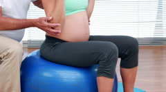 Pregnant woman lifting dumbbells on an exercise ball Arkistovideo