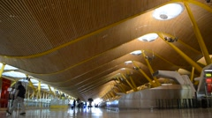 Passengers with luggage in the modern Terminal 4 of Madrid International Airport Stock Footage