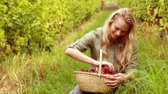 Blonde winegrower handing a red grape Stock Footage