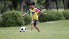 Young asian boy playing soccer in a park, Bangkok Thailand Stock Footage