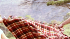 Cute couple setting up the picnic blanket Stock Footage