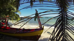 Tropical island beach view, with wooden boat, palm trees and pier in background. Stock Footage