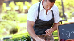 Farmer man tidying up a table of local food Stock Footage