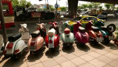 Old vintage motor scooters standing for sale on road side, against city traffic Stock Footage