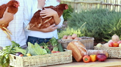 Smiling farmer couple holding chickens - stock footage
