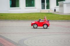 Beautiful little girl riding toy car in summer park - stock photo