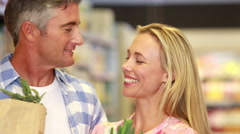 Happy couple with paper bags embracing - stock footage