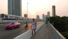 People and car move on the bridge, sunset dusk, bright sun disc Stock Footage