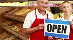 Smiling workers holding open sign - stock footage