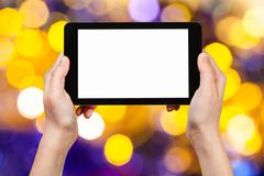 Hand with tablet pc on yellow and violet background Stock Photos