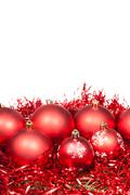 several red Xtmas baubles and tinsel isolated - stock photo