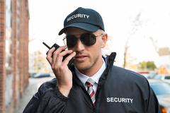 Portrait Of Young Male Security Guard Talking On Walkie-talkie - stock photo