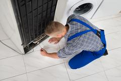 Young Male Repairman Making Refrigerator Appliance In Kitchen Room - stock photo