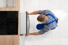 High Angle View Of Man In Overall Repairing Oven In Kitchen Stock Photos
