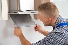 Young Repairman Repairing Kitchen Extractor Filter In Kitchen Room - stock photo