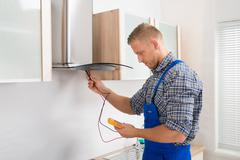 Male Worker In Overall Testing Kitchen Hood With Multimeter In Hands Stock Photos
