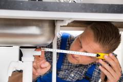 Male Plumber In Overall Measuring Sink Pipe With Measuring Tape Stock Photos
