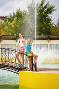 Best friends standing on the bridge near the fountain. - stock photo