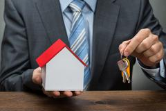 Businessman With Keys And House Model - stock photo