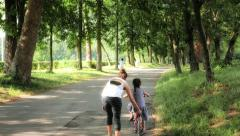 Mom teaching bicycle to her daughter - stock footage