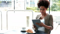 College student using tablet at campus cafe - stock footage