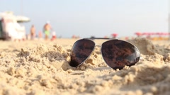 Points lying on the sand. In the glasses reflected the sun Stock Footage