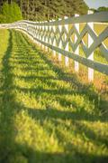 White fence leading up to a big red barn Stock Photos