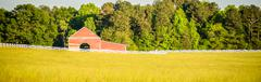 white fence leading up to a big red barn - stock photo