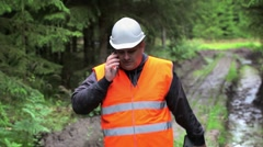 Forest officer talking on cell phone on rutted forest road Stock Footage