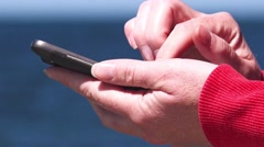 Female hands using mobile smart phone at ocean pier Stock Footage