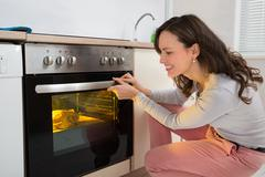 Happy Woman Roasting Chicken Meat In Kitchen Oven Stock Photos