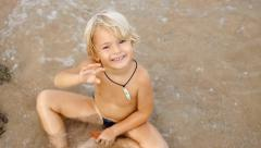 Overhead shot of little cute smiling child playing in blue sea, waving hand. Stock Footage