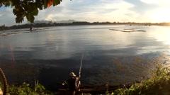 Man fishing rod on lake at sundown Stock Footage