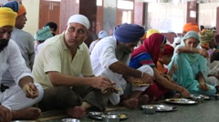 Beggar indian people receive a free meal in Sikh Golden Temple, Amritsar. India Stock Footage