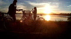 Friends bicycle at lakeshore at sundown Stock Footage