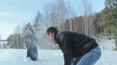 Couple having snowball fight in snow in winter forest Stock Footage