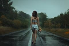 Girl back. Walks on the road. Under rain. Stock Photos