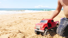 Black toddler playing with a red truck on the beach Stock Footage