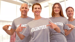Group of Volunteers pointing at shirts Stock Footage