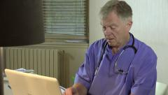Dentist checks his appointments on his computer - stock footage