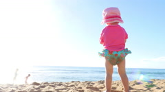 Cute blonde toddler playing on a beach Stock Footage