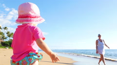 Cute blonde toddler walking on a beach Stock Footage
