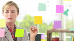 Blonde designer looking at post its on window Stock Footage