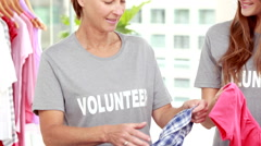 Smiling friends volunteers separating clothes Stock Footage